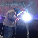 Welder Repairing Hole In Side Of Ship